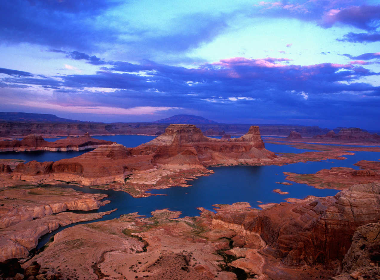 Lake Powell in the Glen Canyon Recreation Area is a large desert lake surrounded by magnificent red rock cliffs.